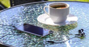 En kaffekopp och en Iphone på ett bord.